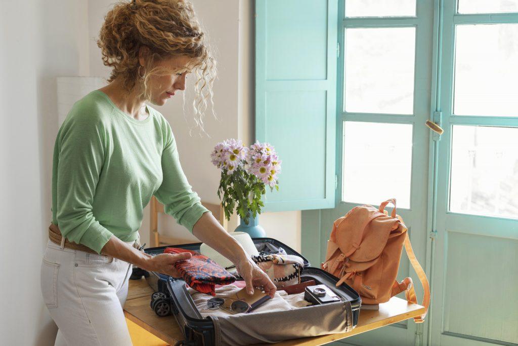 mulher turista arrumando a mala de viagem