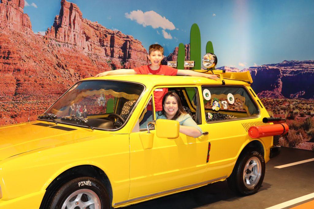 mae e filho se divertindo na brasilia amarela dos mamonas assassinas no parque tematico Movie Cars