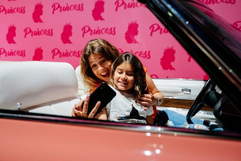 mãe e filha no cenário das princesas e tirando foto no cadillac rosa